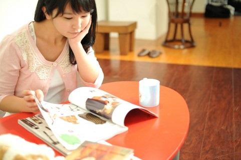 雑誌をめくり思考をめぐらす女性