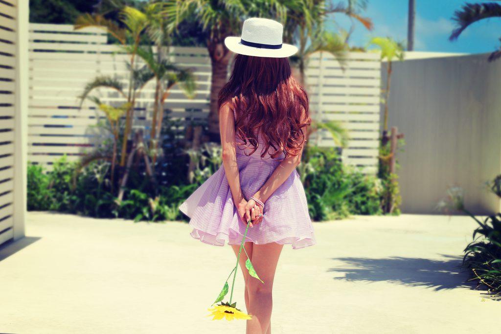 後ろ手にひまわりを持って歩いている女の子