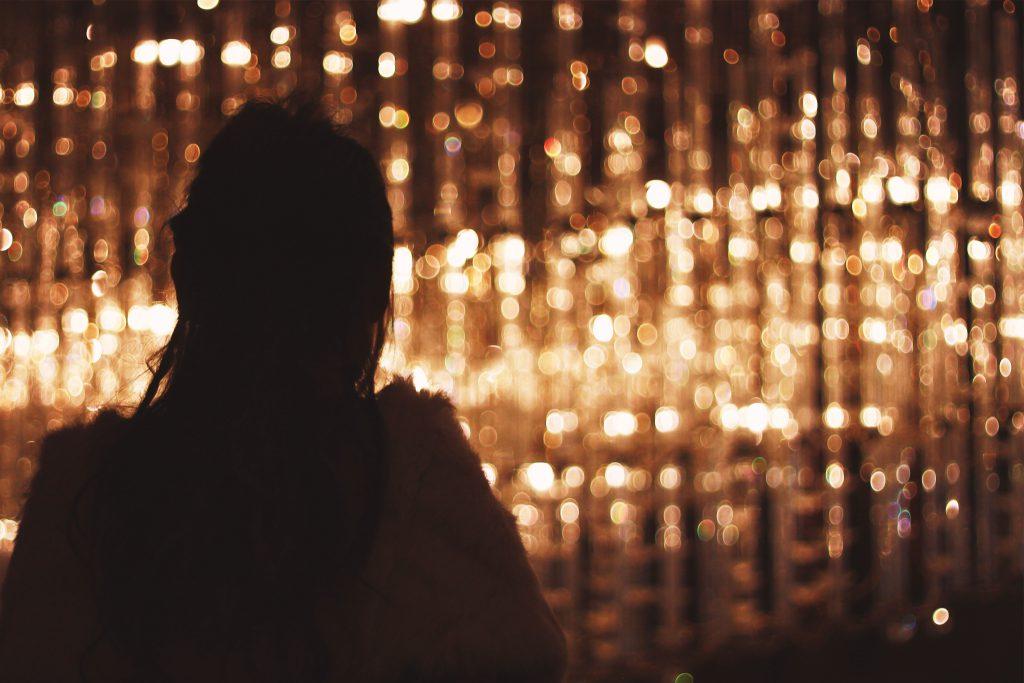 大きなシャンデリアを眺めている女の子のシルエット