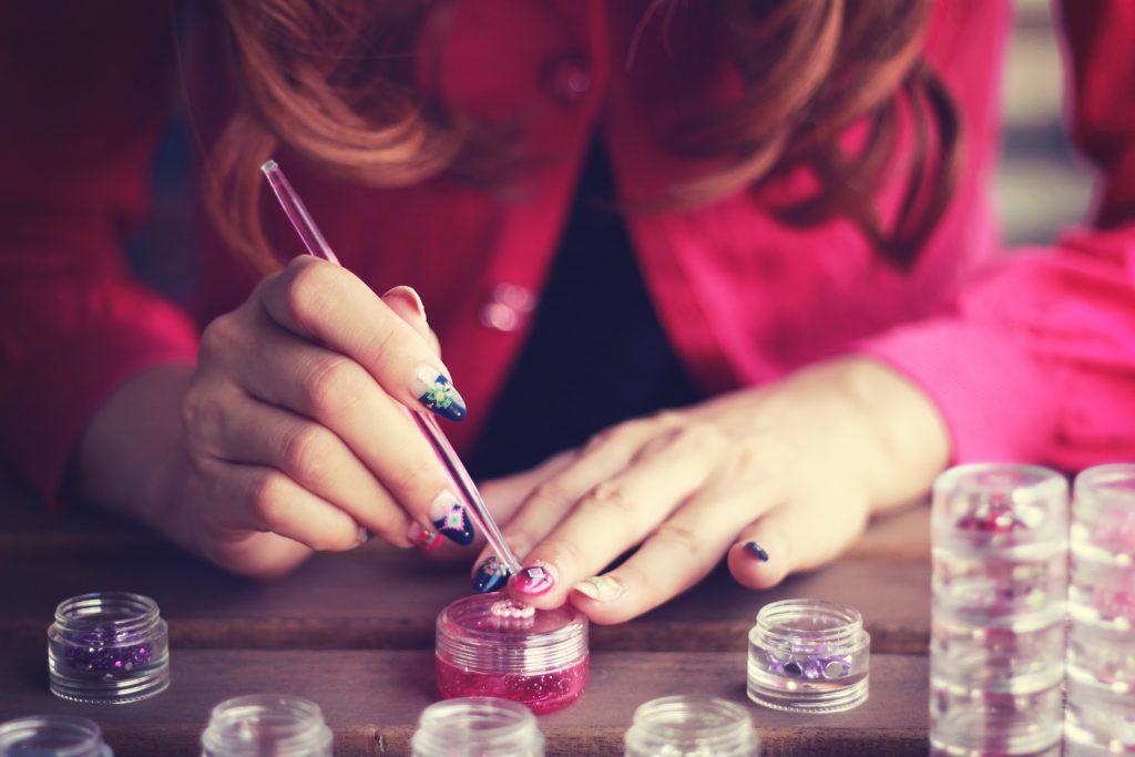 自分のネイルを見せてデザインを説明するネイリストの女の子