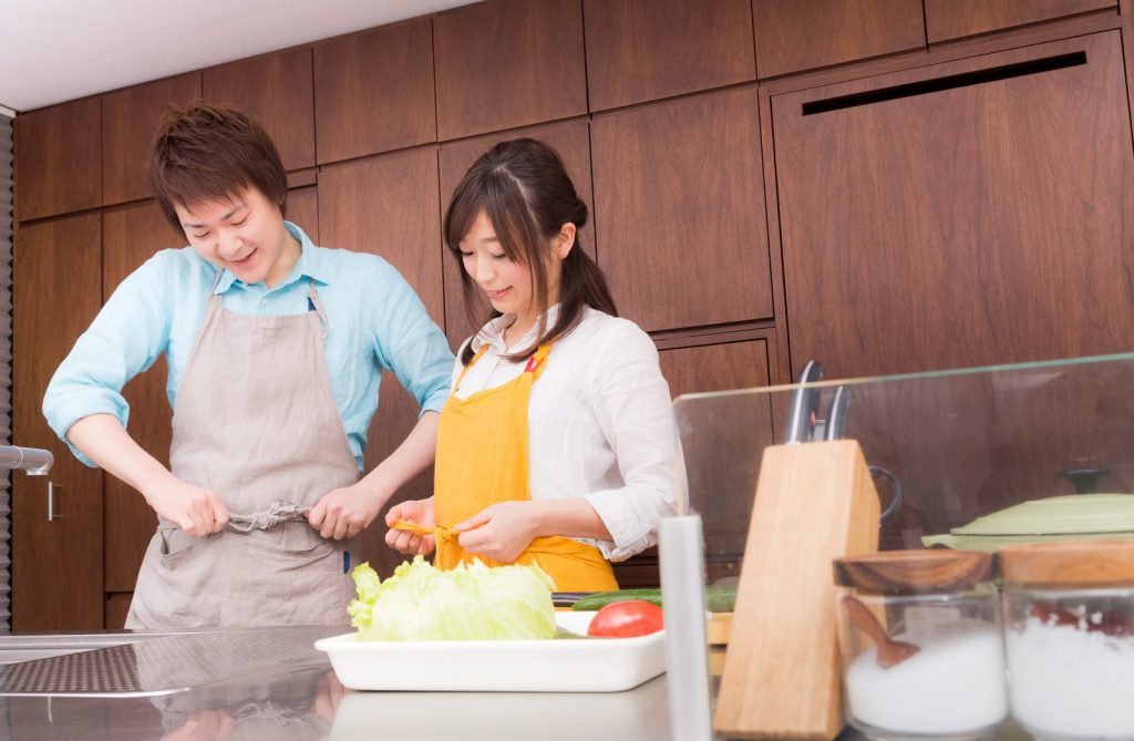エプロンをして料理の下準備をはじめる夫婦