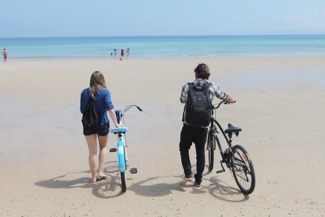 砂浜で自転車を持って歩くカップル