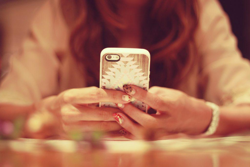 机でスマートフォンを操作する女の子