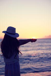 落ちてくる夕陽を手のひらですくっている女の子