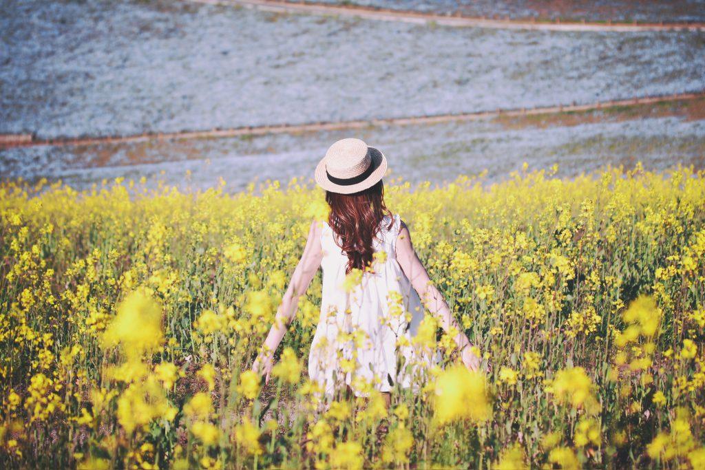 菜の花畑の間に立っている女の子