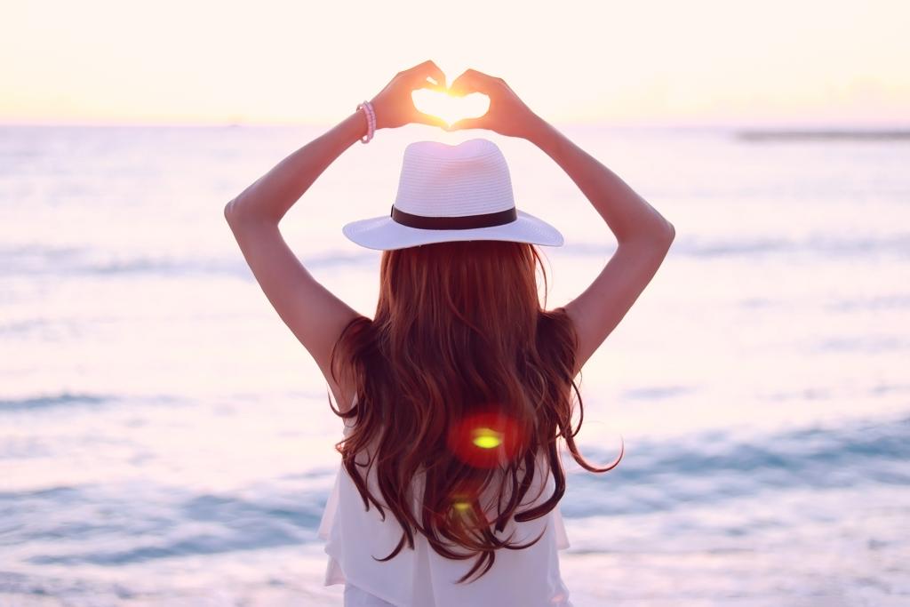 海に落ちていく夕陽にハートの手をかざす女の子