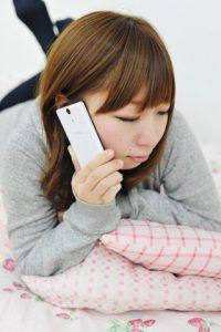 寝転がりながら電話で話す女性