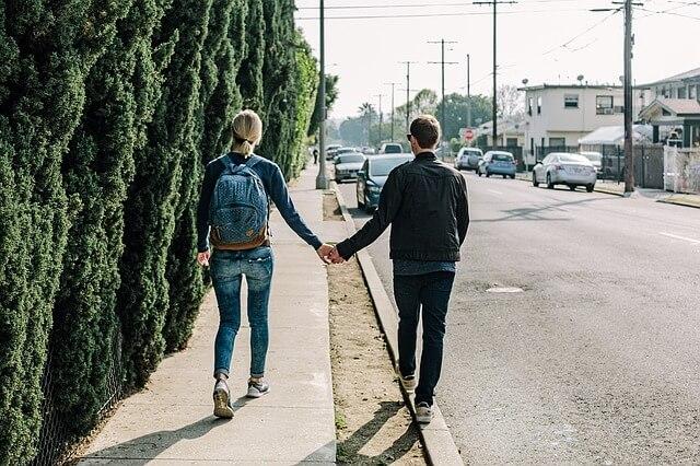 手をつないで歩道を歩くカップル