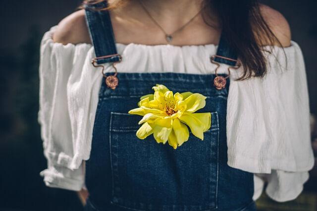 胸ポケットに黄色い花を入れて歩く女性