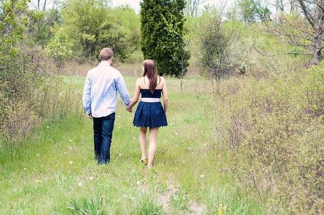 原っぱで手をつないで歩くカップル