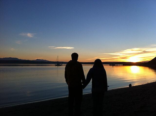 夕日の見える湖で手をつなぐカップル