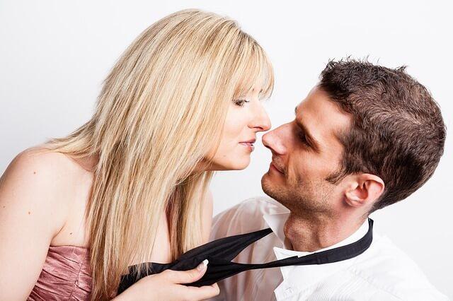 男性のネクタイを緩めキスを迫る女性