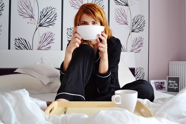 ベッドでシリアルボウルを持つ少女
