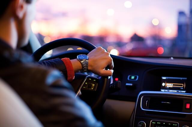 夕暮れに車を運転する男性