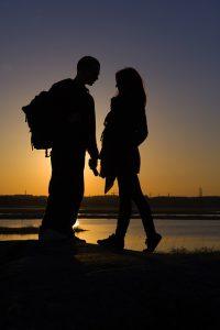 日の入りに手をつなぐカップル