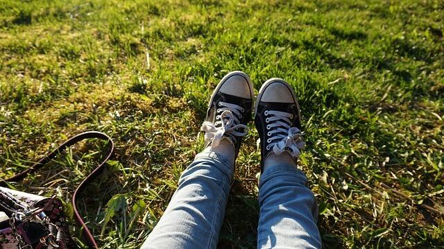 芝生で伸ばされた足