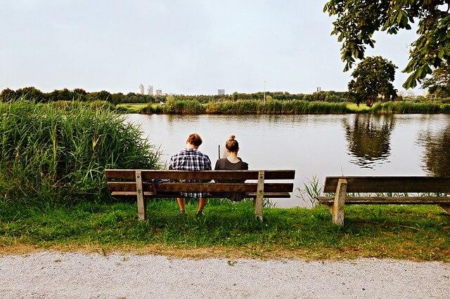川辺のベンチで話すカップル