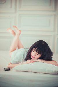 ベッドで横たわる女性