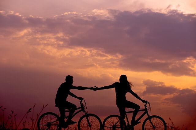 夕暮れにサイクリングするカップル