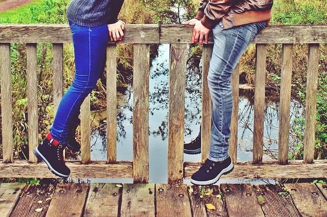 橋をまたいで座るカップル