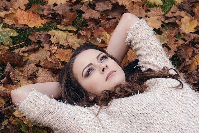 落ち葉の上で仰向けになる女性