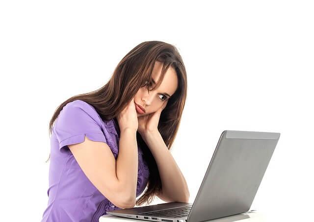 パソコンを見ながら悩む女性
