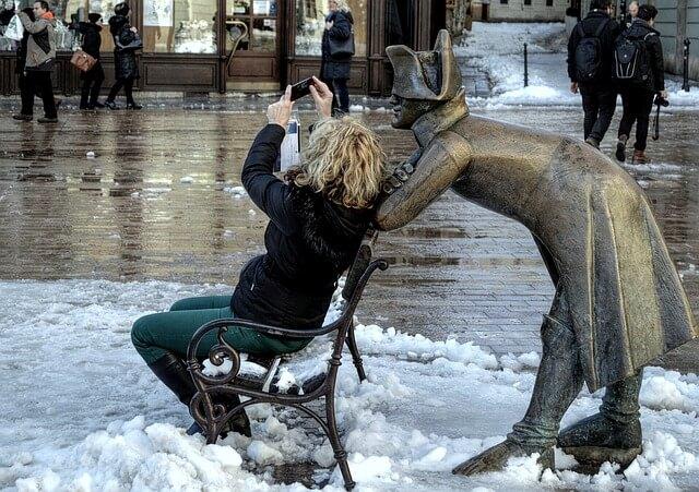 彫像のあるベンチに座る女性