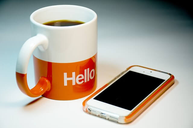 スマホとコーヒーの入ったコップ