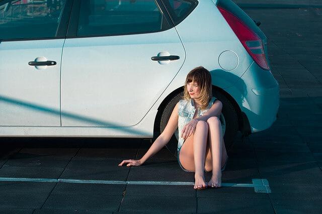 車の前で体育すわりする女性