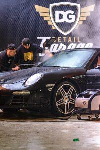 黒い高級車を洗車する男性