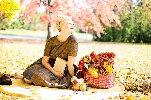 紅葉した木の下で本を読む女性