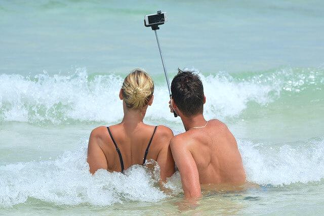 浜辺でセルフィーするカップル