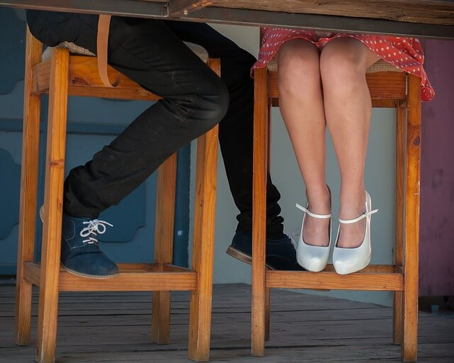 椅子に座っているカップルの足