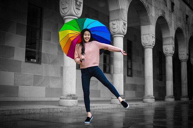 カラフルな傘を差し笑顔な女性