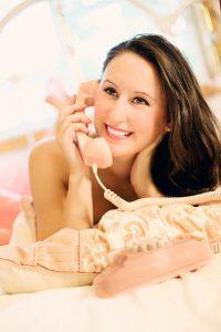 ベッドで横になりながら電話する女性