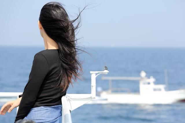 遠くの海を見つめる女性