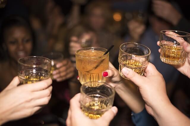 お酒の入ったグラスを持ち乾杯する男女