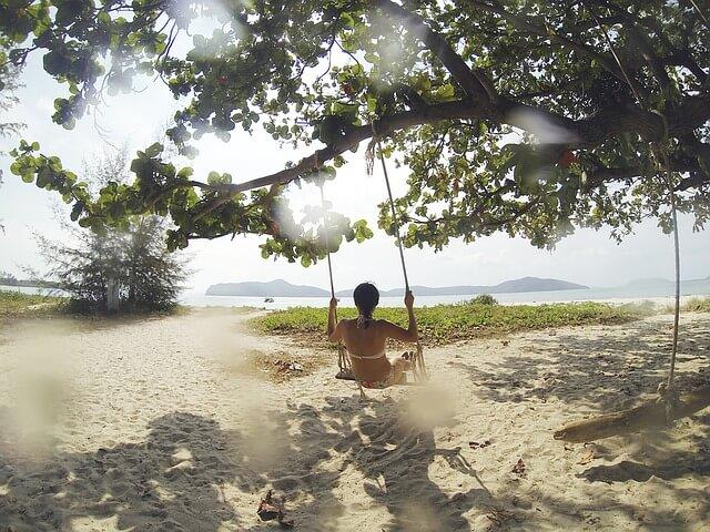 熱帯のビーチでブランコに揺られる女性