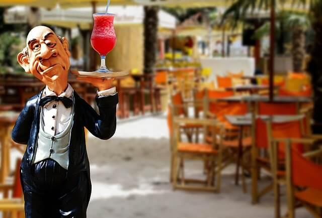 レストランでカクテルを運ぶウェイター