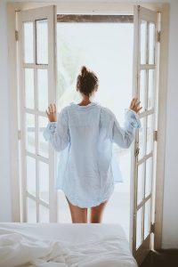 朝に窓を開けて日の光を浴びる女性
