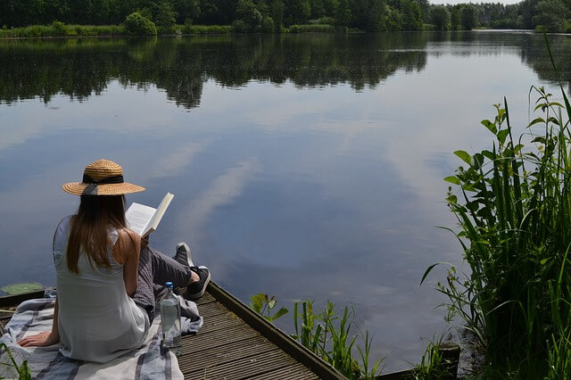 湖のほとりで本を読む女性