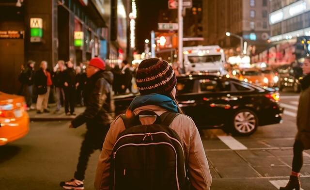 ナップザックを背負って一人で街を歩く女性