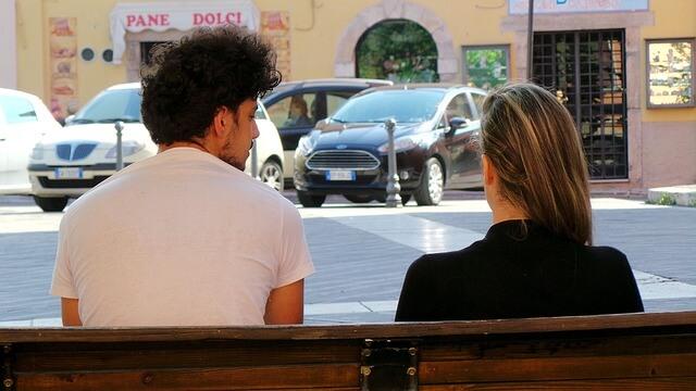 ベンチに座って話す男女