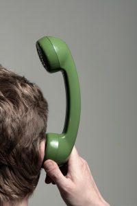 受話器を耳に当てる男性