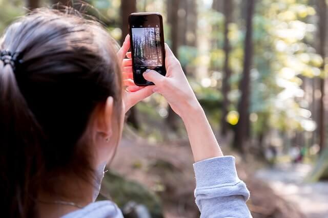 景色の写真をスマホで撮る女性