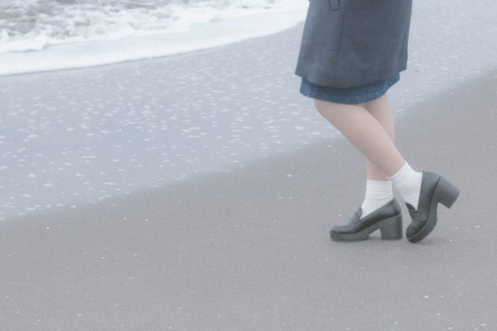 波打ち際でたたずむ女性