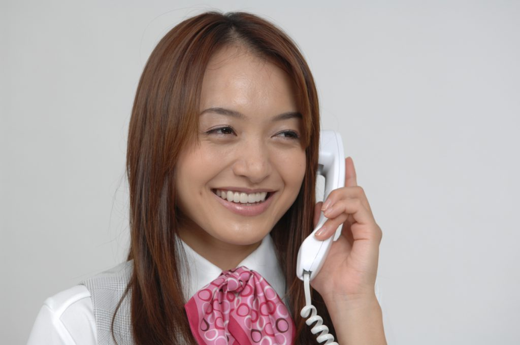 テンション高く電話応対する女性