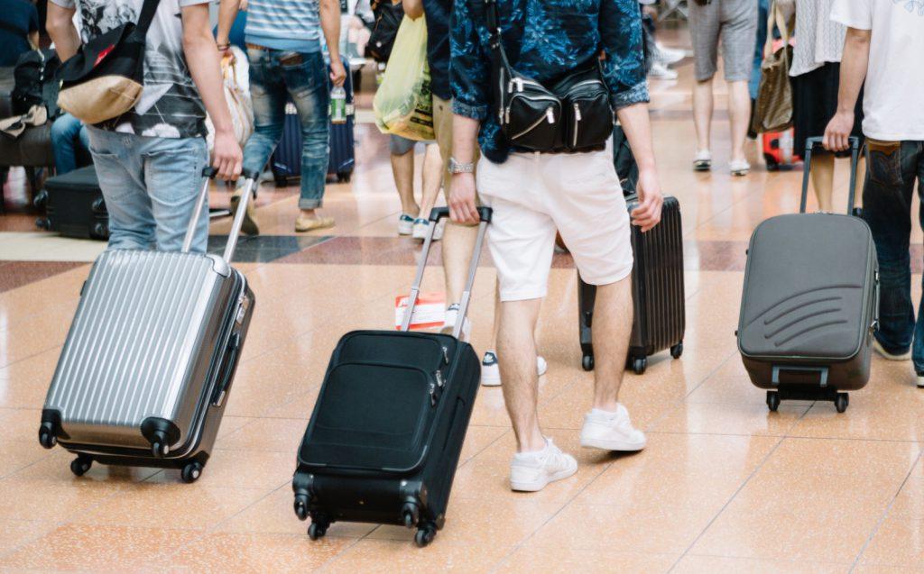 キャリーバッグを持ち旅行でかけるカップル