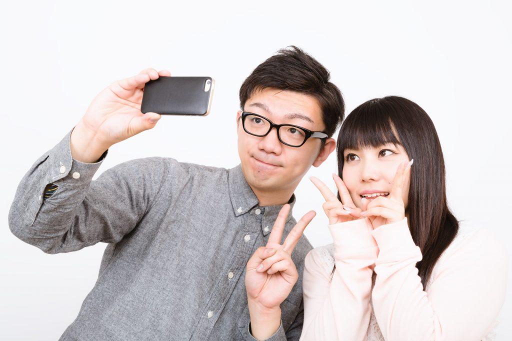デート中に笑顔で写真を撮るカップル