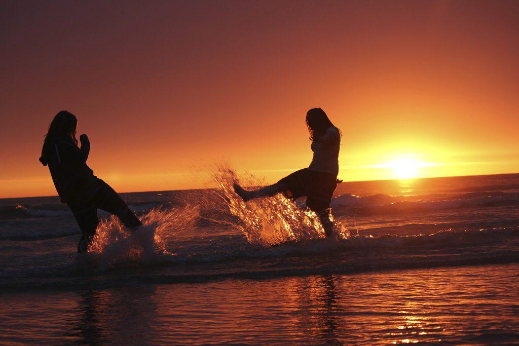 海辺で親友と遊ぶ女性